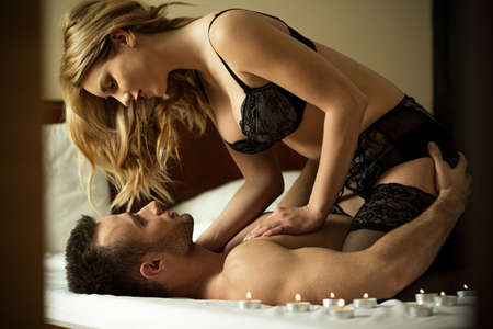 enamorados en la cama: Los pares cariñosos tener momentos de intimidad en el dormitorio Foto de archivo