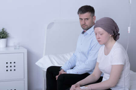 neoplasm: Worried girl with cancer and her helpful loving dad Stock Photo