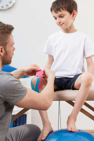 broken knee: Little patient having applied kinesiology tapes on the knee