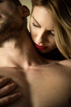 страстный: Женщина целует шею любовника вот миг романтического прелюдии Фото со стока