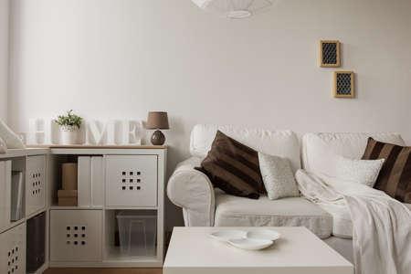 Witte bank en bruine kussens in de woonkamer