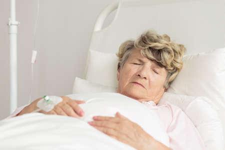 Senior sick woman sleeping in hospital bed