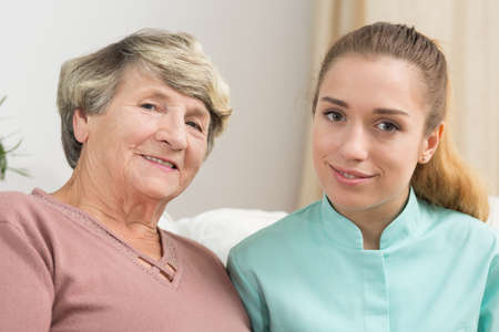 dignity: Portrait of smiling elderly woman and helpful caregiver Stock Photo