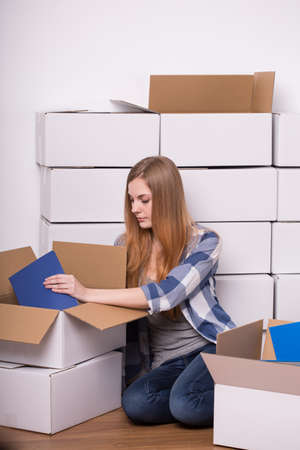carefully: Young pretty woman carefully packing book to boxes Stock Photo