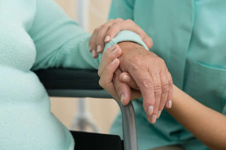 cares: Photo of nurse supporting old woman on wheelchair Stock Photo