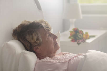 tired: Ill tired elderly woman thinking in loneliness in hospital
