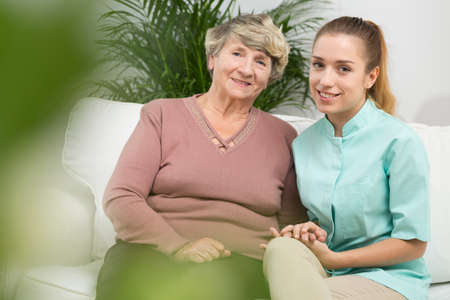 senility: Image of happy old female with professional caregiver Stock Photo
