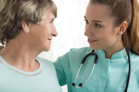 senescence: Portrait of nurse with stethoscope supporting elderly woman