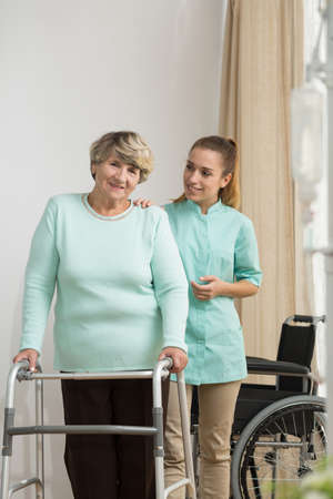home safety: Picture of senior lady with walking problems and helpful carer