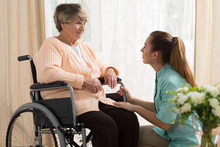 휠체어에 나이 든 여성을 돕는 간병인의 그림