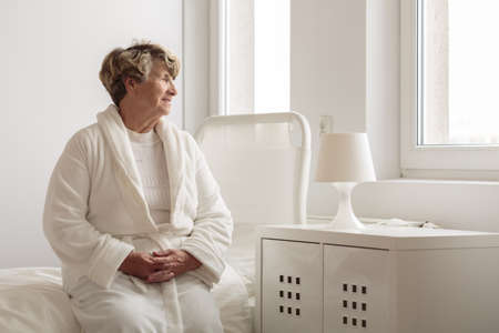 Lonely senior woman in dressing-gown in empty hospital room