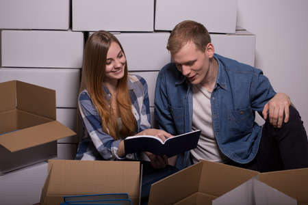 moving out: Married young couple reading found book during moving out