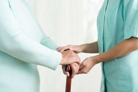 disabled seniors: Close up of caregiver holding hand of old female Stock Photo
