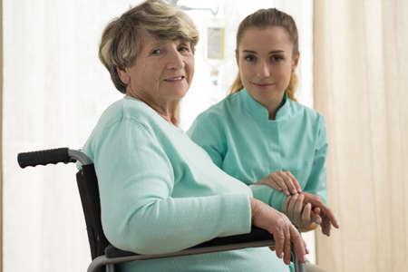 Foto van verpleegkundige zorg over senior dame met wandelen problemen