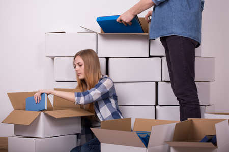 moving out: Young couple hiding the books to cartons during moving out Stock Photo