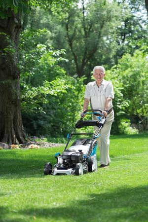 elder tree: Image of elder gardener mowing green lawn