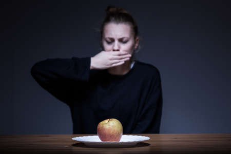 anorexia: Woman with anorexia refusing to eat an apple Stock Photo