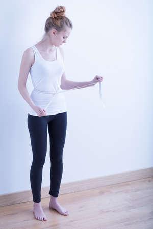 skinny woman: Skinny young girl measuring her waist circumference
