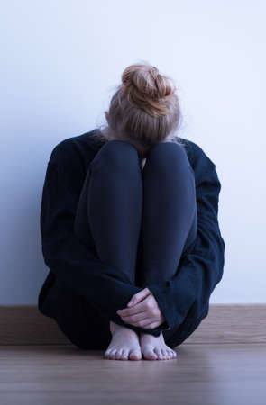 lonely: Broken down, lonely, young woman sitting on the floor Stock Photo