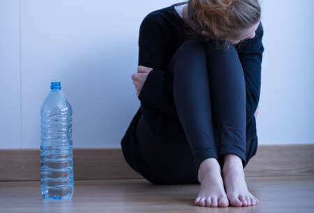 trastorno: Muchacha triste anoréxico flaco y una botella de agua Foto de archivo