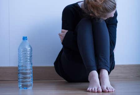 mujer triste: Muchacha triste anoréxico flaco y una botella de agua Foto de archivo