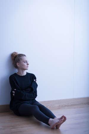 Sad girl in black sitting alone in empty room