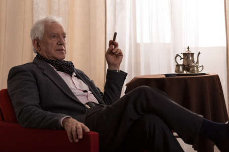 wealth: Man enjoys his time and he is smoking a cigar Stock Photo