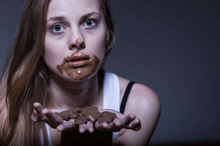 obsession: Bulimic girl eating chocolate snack with obsession