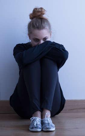 彼女の部屋に一人で座っている孤独な悲しい少女