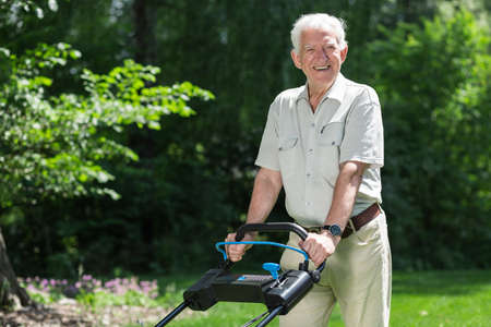 gardening: Smiling retiree cutting grass with lawn mower Stock Photo
