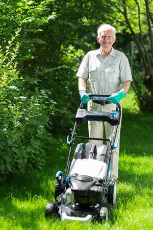 Elder man cutting grass with lawn mower