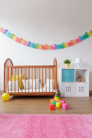 babygirl: Photo of babygirl contemporary bedroom with wooden crib Stock Photo
