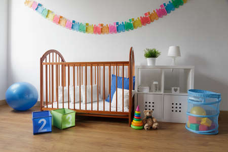Photo of simple design wooden cradle in cosy baby bedroom