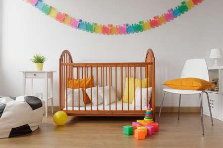 babyboy: Image of newborn bright bedroom with wooden crib