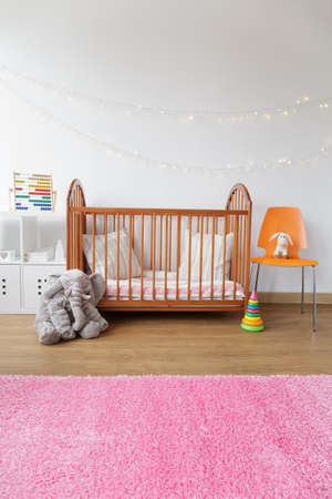Image of child room with wooden crib and pink carpet Stock Photo