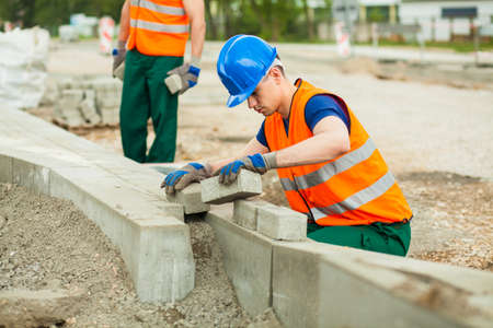 concrete blocks: Horizontal view of young paver at work