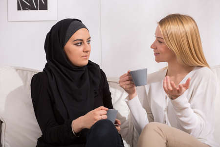 Pretty blond caucasian woman drinking tea with muslim Stock Photo