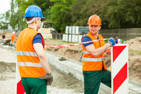 Road construction workers in safety waistcoats and helmets