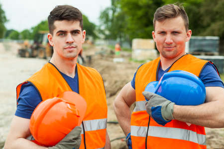 worker construction: Photo of handsome constructive workers holding safety helmets Stock Photo