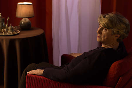 wistful: Lonely elder lady sitting on the armchair Stock Photo