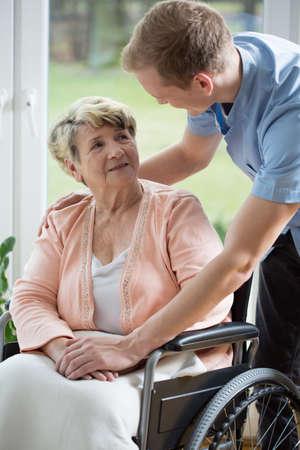 silla de rueda: Enfermera de sexo masculino y mujer mayor en silla de ruedas