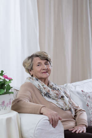 Elegante oudere dame op de bank zitten