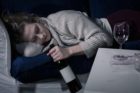 poor woman: Tired drunk woman sleeping with bottle of wine Stock Photo