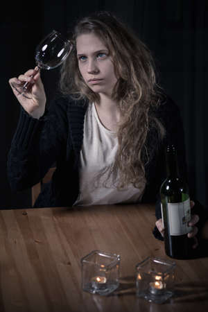 forlorn: Young alcoholic woman looking at clean glass