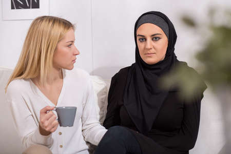 nationalities: Scared blond woman and her worried muslim friend
