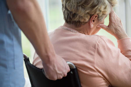 mirada triste: Mujer mayor triste en silla de ruedas en el hogar Foto de archivo