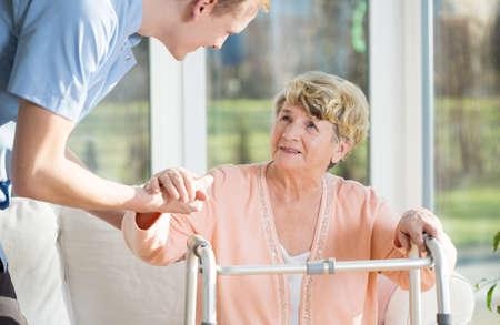 enfermeria: El hombre ayuda a ponerse de pie una mujer mayor en el hogar de ancianos Foto de archivo