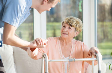 male senior adult: Man helps to stand up an older woman at nursing home Stock Photo