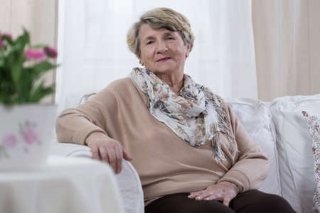 Melancholic elderly pensioner sitting on the sofa