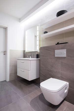 llave de agua: Azulejos grises en el baño en casa moderna